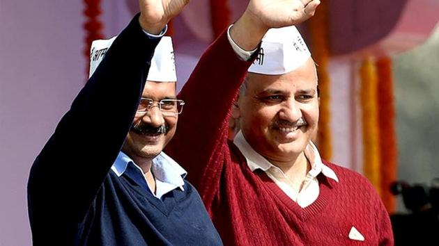 Delhi chief minister Arvind Kejriwal with his deputy, Manish Sisodia (R), greeting supporters during his swearing-in ceremony on February 14, 2015 at Ramlila Ground in New Delhi.(AFP Photo)