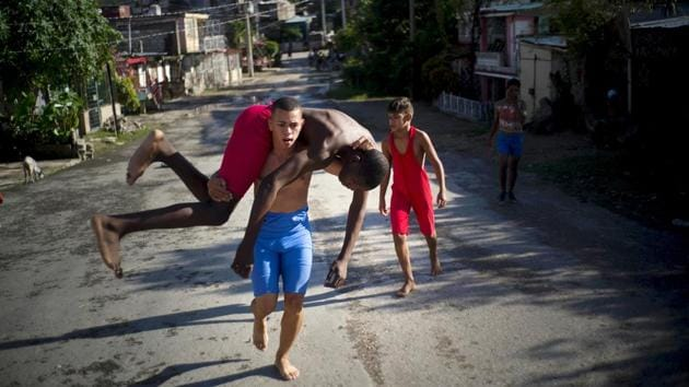 """Wrestlers train in the street during championship week. Two years ago, Heredia Marrero, 55, started bringing children to Chicharrones for training and a tournament. """"We did it on the spur of the moment, in a pretty improvised way,"""" he said. """"We didn't have referees or all the equipment we needed, but finally everyone got behind it."""" (Ramon Espinosa / AP)"""