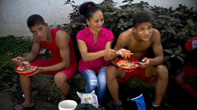 Nalis Mendoza slices a tomato as she feeds her sons, both participants in the wrestling championship. Local doctors and nurses volunteer their time to monitor the wrestlers' health and treat any injuries, while neighbourhood children help by gathering wood to feed stoves feeding the participants in this community affair. (Ramon Espinosa / AP)