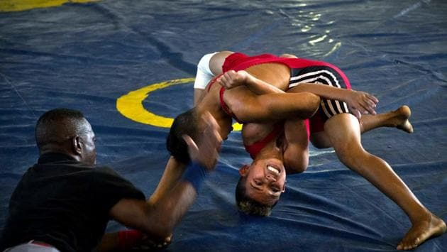 A referee, like the others trained by local sports schools for the event, prepares to pound on the mat if either wrestler's back touches the mat. The more than 150 young wrestlers were divided into teams from various provinces across Cuba and the Chicharrones neighbourhood itself. (Ramon Espinosa / AP)