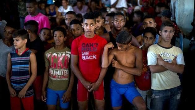 """Young wrestlers stand still during a priest's prayer at the start of a championship coined """"The truth of my neighbourhood,"""" in the Chicharrones neighbourhood of Santiago, Cuba. In this neighbourhood, a wrestling-loving local man created a homegrown, neighborhood-backed program to support aspiring wrestlers from Cuba's economically struggling provinces. (Ramon Espinosa / AP)"""