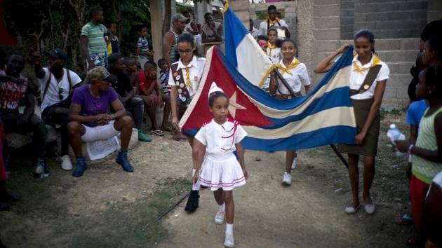 Girls parade a Cuban flag during the opening ceremony for the week-long student wrestling championship. Cuban sporting efforts have been entirely state-run, with talented children entering government programs early and spending their young adult lives in the arms of an official program that focuses their every minute on athletic glory. (Ramon Espinosa / AP)