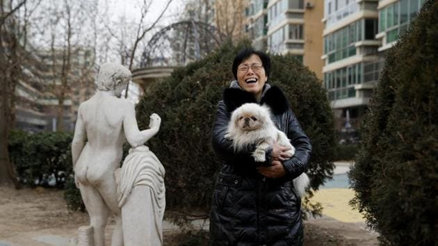 Hu Yujie poses for pictures with her Pekingese dog, Xiaobai, outside her house in Beijing.(REUTERS)