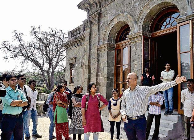 Abhijit Ghorpade, SPPU's official spokesman, explaining the history of SPPU's main building during the heritage walk.(RAVINDRA JOSHI/HT PHOTO)