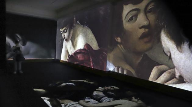 Visitors look at a multimedia projection of the work of Italian master Michelangelo Merisi da Caravaggio (1571-1610) during the opening of a Caravaggio exhibit at the National Art Museum in Mexico City.(AP)