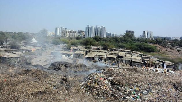 Schoolchildren walk past an illegal garbage dump yard at Wagholi. Residents say chronic garbage burning is leading to pollution of air and water.(Shankar Narayan/HT)