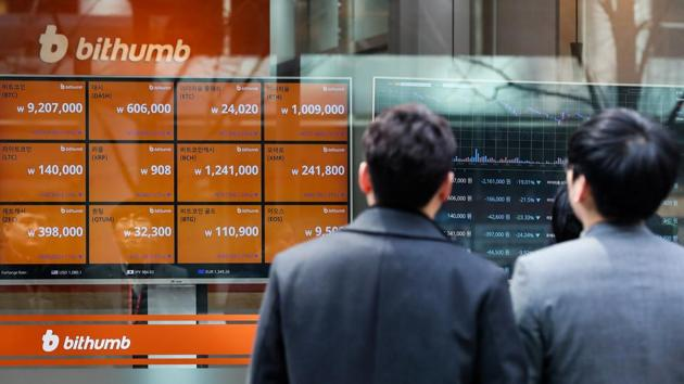Pedestrians look at monitors showing the prices of virtual currencies at the Bithumb exchange office in Seoul.(Bloomberg via Getty Images)