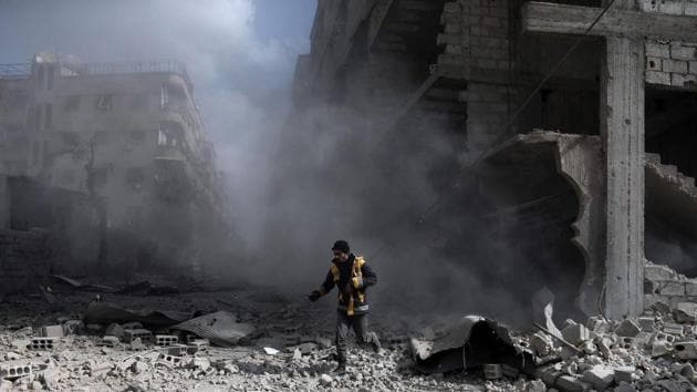 A White Helmets volunteer, checks the site of a regime air strike in the rebel-held town of Saqba, in the besieged Eastern Ghouta region.(AFP Photo)