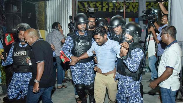 This picture taken on February 21, 2018 shows Maldivian police officers detaining an opposition protestor (C) demanding the release of political prisoners during a protest in Male.(AFP Photo)