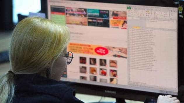 """File photo of an employee of a Santa Cruise 'digital laundry' company monitoring a computer screen to find 'revenge porn' at the company in Seoul. The company is tasked with taking down videos posted without consent — including so-called """"revenge porn"""".(AFP)"""