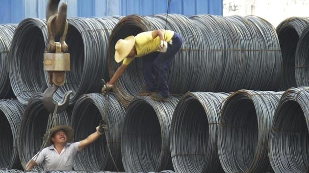 """In this August 1, 2016 file photo, labourers work in the steel market in Yichang in central China's Hubei province. China says it """"firmly opposes"""" US President Donald Trump's tariff increase for imported steel and aluminium but gave no indication whether Beijing might impose its own measures in response. A government statement issued Friday, March 9, 2018, accused Trump of damaging the global trading system.(AP)"""