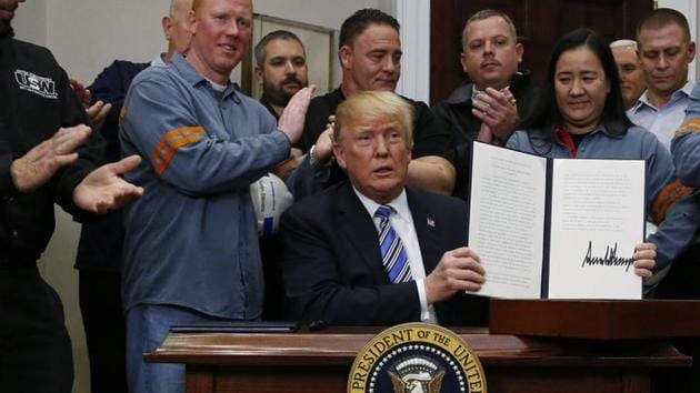 US President Donald Trump holds up a proclamation during a White House ceremony to establish tariffs on imports of steel and aluminium at the White House in Washington, on Thursday.(Reuters photo)
