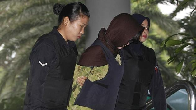 Vietnamese Doan Thi Huong, center, is escorted by police as she arrives for a court hearing at the Shah Alam High Court in Shah Alam, Malaysia, on March 20, 2018.(AP Photo)