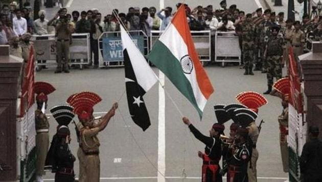 Pakistani rangers (wearing black uniforms) and Indian Border Security Force (BSF) officers lower their national flags during a daily parade at the Pakistan-India joint checkpost at Wagah border on November 3, 2014.(Reuters)