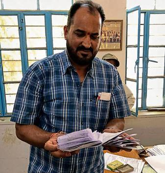 Prof Chandra Shekhar Sharma, head of an anti-copying flying squad of Udaipur's Mohanlal Sukhadia University, with 128 cheat sheets of printed answers .(HT Photo)
