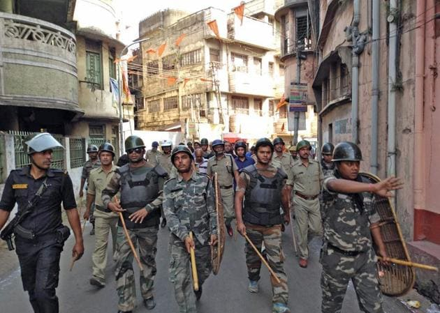 Police force flag march at clash-hit Ranigunj area at Burdwan district of West Bengal on Tuesday.(PTI Photo)