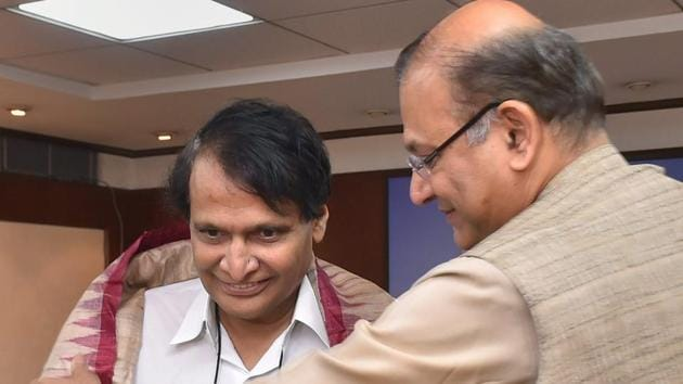 New civil aviation minister Suresh Prabhu being welcomed by MoS Jayant Sinha at his office at Rajiv Bhawan in New Delhi.(PTI Photo)