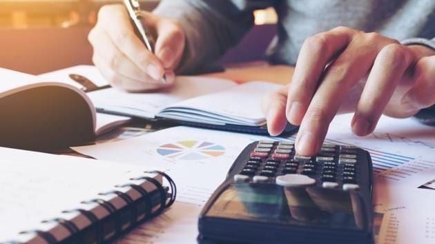 Close up hand man doing finance and calculate on desk about cost at home office.(Getty Images/iStockphoto)