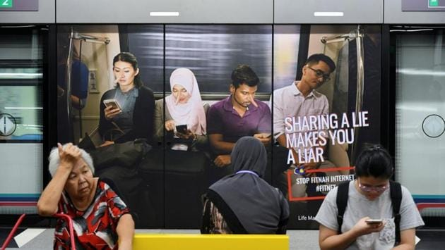 Commuters sit in front of an advertisement discouraging the dissemination of fake news, at a train station in Kuala Lumpur, Malaysia, on March 28.(Reuters File Photo)