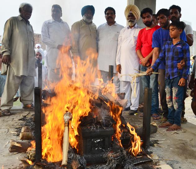 11-year-old son, Karan, light his father Sonu's prye at a cremation ground in Chawinda Devi village, 20 km from Amritsar city.(Sameer Sehgal /HT)