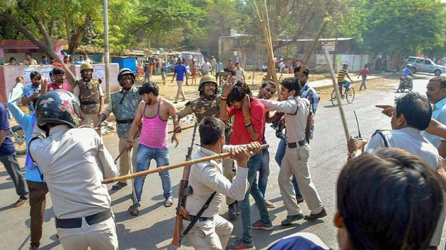Police personnel lathi charge a protestor during 'Bharat Bandh' against the alleged 'dilution' of Scheduled Castes/Scheduled Tribes act in Gwalior on Monday.(PTI Photo)