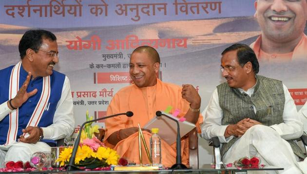 """Uttar Pradesh chief minister Yogi Adityanath with his deputies Keshav Prasad Maurya and Dinesh Sharma at a programme at his residence to distribute cheques to the pilgrims of """"Kailash Mansarovar and Sindhu Darshan"""" yatra in Lucknow. The cabinet led by Adityanath also decided to prorogue the two houses of the state assembly following end of the budget session.(PTI File)"""