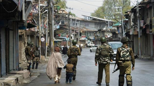 CRPF personnel patrol a street during the third day of strike over the killings of militants and civilians in three separate encounters in Kashmir, in Srinagar, on Tuesday.(PTI Photo)