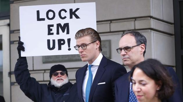 Alex van der Zwaan leaves Federal District Court in Washington, Tuesday, April 3, 2018. Holding the sign up is Bill Christeson from the Washington area.(AP)