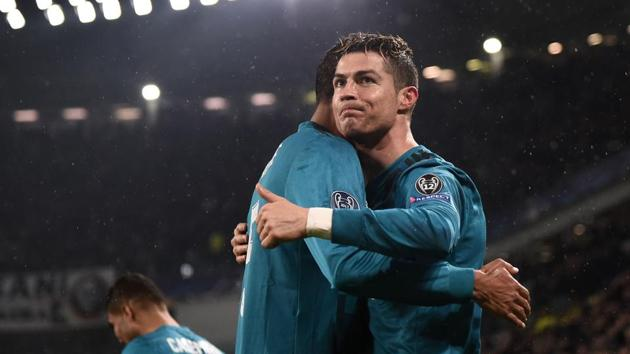 Real Madrid's Portuguese forward Cristiano Ronaldo (R) celebrates with defender Raphael Varane after scoring his team's second goal during the UEFA Champions League quarter-final first leg football match vs Juventus at the Allianz Stadium in Turin on Tuesday.(AFP)