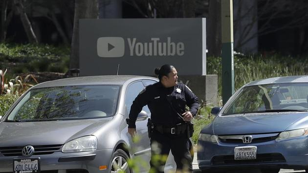 An officer runs past a YouTube sign near the company's complex in San Bruno, California, on April 3, 2018.(AP)