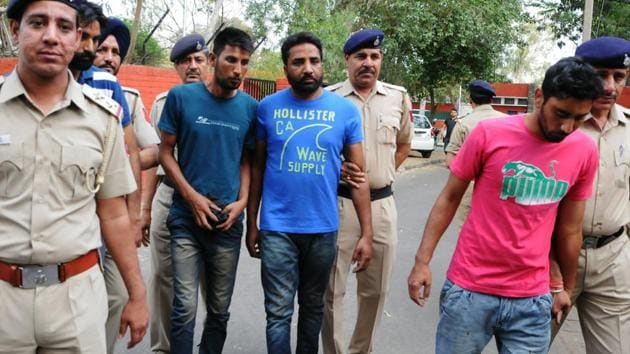 Yodha Singh (in pink T-shirt) and his other accomplices in police custody at crime branch Sector 11, Chandigarh on Thursday.(HT Photo)