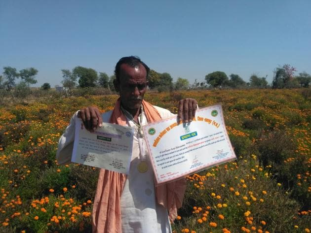 Farmer Bala Raikwar standing in his agriculture field with a certificate of the best farmer of his block given to him by the administration(HT photo)