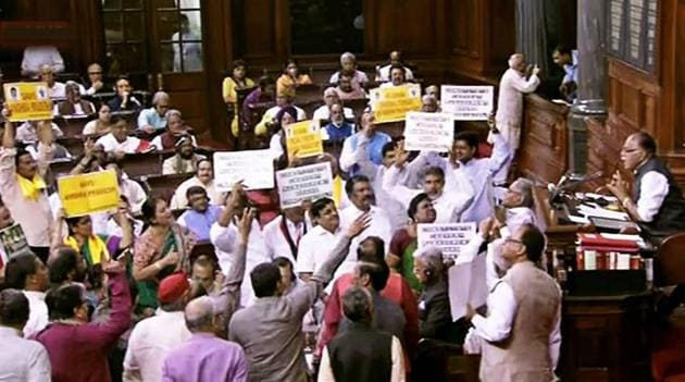 Opposition members protest in the well of the Rajya Sabha on Thursday.(PTI photo)