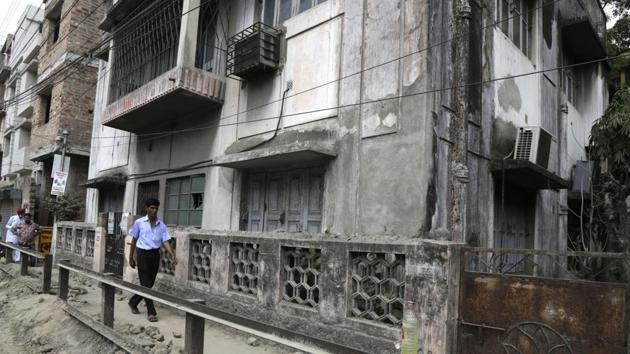 A man walks past the house where Subhabrata Majumdar had allegedly kept his mother's body in a freezer for almost three years in Kolkata.(AP Photo)