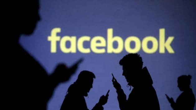 Silhouettes of mobile users next to a screen projection of Facebook logo in a picture illustration, March 28, 2018.(REUTERS)