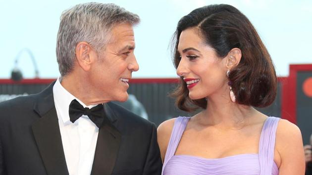 George Clooney, left, and his wife Amal Clooney pose for photographers upon arrival at the premiere of the film Suburbicon during the 74th edition of the Venice Film Festival in Venice, Italy.(Joel Ryan/Invision/AP)