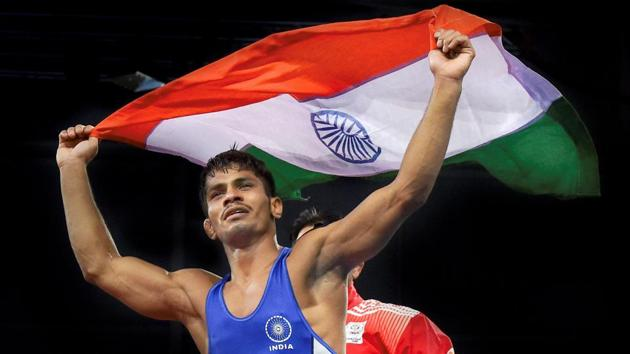 India's Rahul Aware celebrates with the tricolour after winning gold in the 57kg men's freestyle wrestling division at the 2018 Commonwealth Games in Gold Coast on Thursday.(PTI)