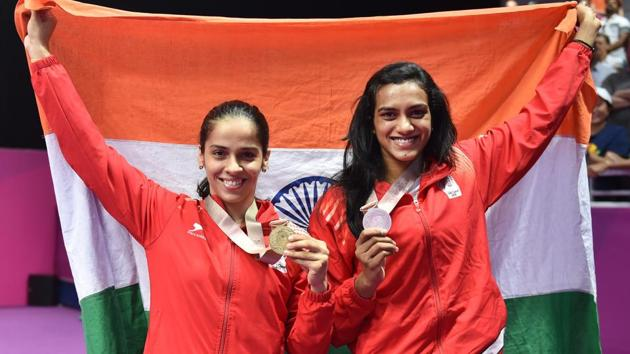 Women's singles gold medallist Saina Nehwal and silver medallist PV Sindhu during the medal ceremony at the 2018 Commonwealth Games in Gold Coast, Australia on Sunday.(PTI)