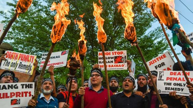 Members of RTI Movement and local residents display placards and hold torches during a protest against the rape and murder of 8-year-old girl of Kathua in Jammu, in Srinagar on Saturday.(PTI File Photo)