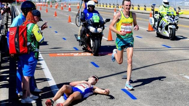 Scotland's Callum Hawkins lies on the ground as Australia's Michael Shelley runs past during the men's marathon final at the 2018 Commonwealth Games in Gold Coast on Sunday.(REUTERS)
