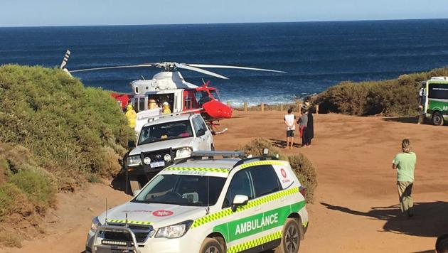 A rescue helicopter and other emergency vehicles are seen at the scene of the shark attack in Gracetown, Australia, Monday.(AP Photo)
