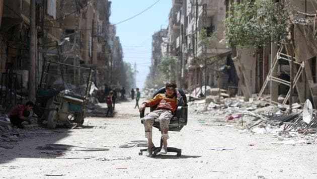 A boy sits on a chair along a damaged street at the city of Douma in Damascus, Syria April 16, 2018.(REUTERS Photo)