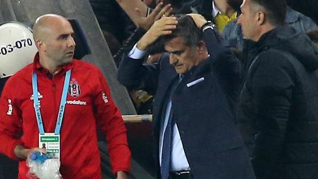 Besiktas head coach Senol Gunes (R) holds his head after being hit by an object during the Turkish Cup semi final second leg football match between Fenerbahce and Besiktas.(AFP)