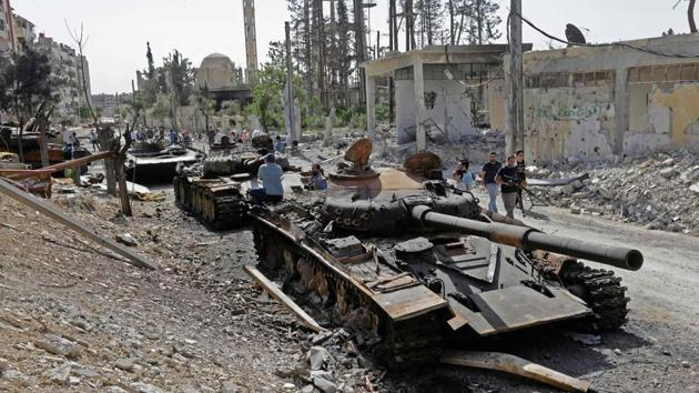 Destroyed tanks and armoured personnel carriers are pictured on a road in the Eastern Ghouta town of Douma on the outskirts of the capital Damascus on April 20, 2018, during an army-organised media tour.(AFP Photo)