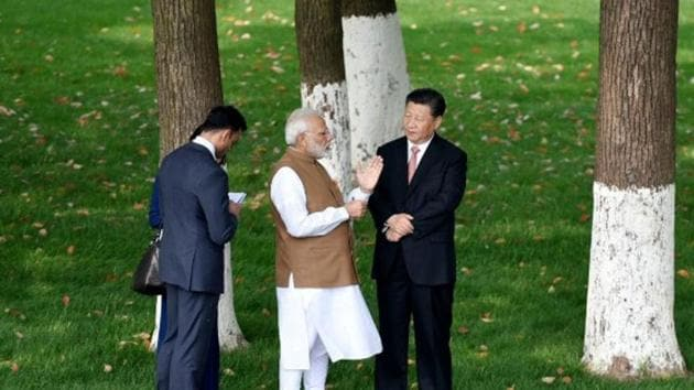 Prime Minister Narendra Modi speaks with Chinese President Xi Jinping as they walk along the East Lake in Wuhan, China, April 28, 2018.(Photo: PIB)