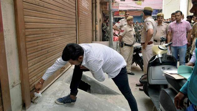 A municipal corporation official seals a shop at Gandhi Nagar during a sealing drive in east Delhi.(PTI FILE)