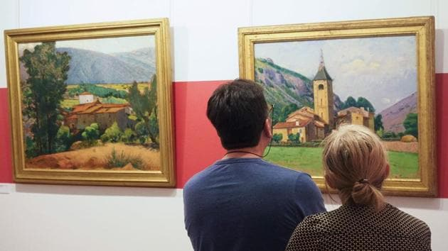 """Visitors look at the painting """"Le clocher de Ria"""" (The bell tower of Ria) at the musuem dedicated to French painter Etienne Terrus, in France.(AFP)"""