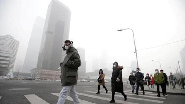 A man wearing a respiratory protection mask walks toward an office building during the smog after a red alert was issued for heavy air pollution in Beijing's central business district, China.(Reuters File Photo)