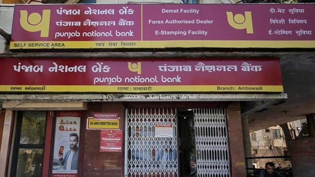 A man reads a newspaper outside a branch of Punjab National Bank in Ahmedabad.(REUTERS)