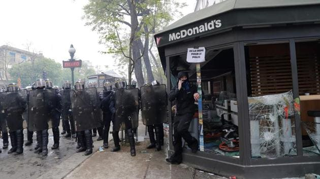 CRS riot police officials stand next to a damaged McDonalds resteraunt during a demonstration on the sidelines of a march for the annual May Day workers' rally in Paris on May 1, 2018.(AFP)
